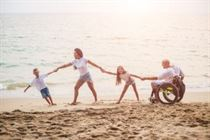 Disabled man on beach with family