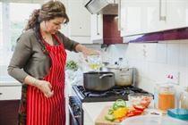 Woman adding oil in kitchen