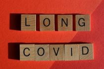 Long Covid spelt out with wooden blocks on red background